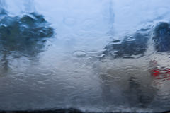Den oskarpa bilkonturn som ses till och med vatten, tappar på bilwindshen Royaltyfri Foto