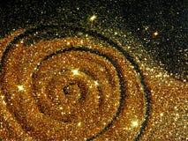 Den oskarpa guld- spiralen av blänker gnistrandet på svart bakgrund arkivfoton