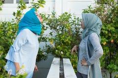 Den oskarpa st?enden av ilskna tv? hijabkvinnor har mots?ttningar arkivbilder