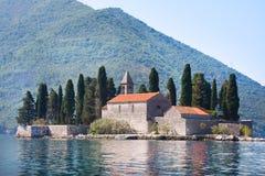 Den Ostrvo Sveti Dorde ön av St George är en av de två holmarna av kusten av Perast i fjärd av Kotor Fotografering för Bildbyråer