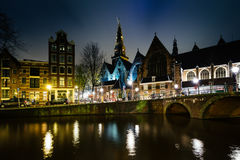 Den Oude kyrkan och en kanal på natten, i Amsterdam, Netherlaen royaltyfri bild