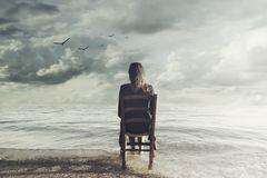 Den overkliga kvinnan ser det oändliga sammanträdet på en stol inom havet royaltyfri fotografi