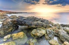 Den overkliga landskaphögen av stenar i havet sköt med en lång exp Arkivfoto