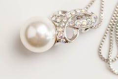 Den pärlemorfärg hängen som isoleras på det vita bakgrundsslutet upp bild av den enkla vita pärlan på kristall och, försilvrar up royaltyfri foto