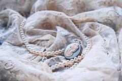 Den pärlemorfärg halsband- och antikvitetkamén snör åt på Royaltyfri Foto