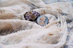 Den pärlemorfärg halsbandet och antika broscher snör åt på Royaltyfri Foto