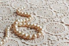 Den pärlemorfärg halsbandet snör åt på tyg Royaltyfri Fotografi