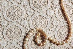 Den pärlemorfärg halsbandet snör åt på tyg Royaltyfria Bilder