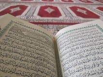 Den på engelska heliga quranen och arabiska på en härlig Östlig-modell utformad filt royaltyfri fotografi