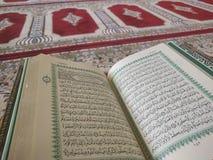 Den på engelska heliga quranen och arabiska på en härlig Östlig-modell utformad filt royaltyfri bild