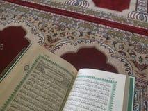 Den på engelska heliga quranen och arabiska på en härlig Östlig-modell utformad filt arkivbild