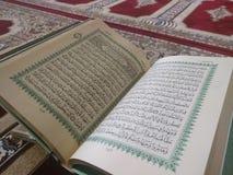 Den på engelska heliga quranen och arabiska på en härlig Östlig-modell utformad filt arkivfoto