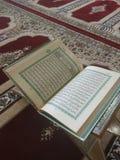 Den på engelska heliga quranen och arabiska på en härlig Östlig-modell utformad filt arkivfoton