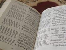 Den på engelska heliga quranen och arabiska på en härlig Östlig-modell utformad filt royaltyfria foton