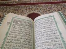 Den på engelska heliga quranen och arabiska på en härlig Östlig-modell utformad filt royaltyfria bilder