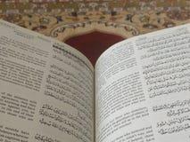 Den på engelska heliga quranen och arabiska på en härlig Östlig-modell utformad filt arkivbilder