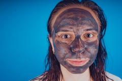 Den pålagda flickan framsidamaskeringen för akne Begreppet av ansiktsbehandlingen royaltyfria foton
