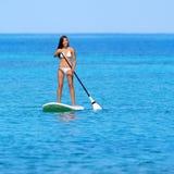 Den Paddleboarding strandkvinnan står på upp paddleboard Arkivfoton