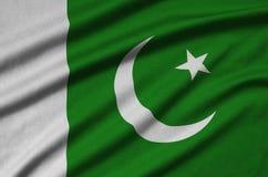 Den Pakistan flaggan visas på ett sporttorkduketyg med många veck Baner för sportlag arkivbilder