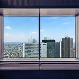 Antennen beskådar av Shinjuku skyskrapor till och med ett fönster inramar. Tokyo Japan. Arkivfoto