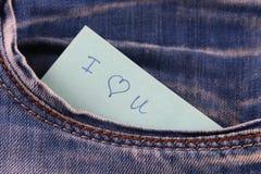 Den pappers- anmärkningen med inskriften älskar jag dig, med förälskelsepip ut ur facket av jeansbyxa Begreppet av dagen av vänne Royaltyfri Bild