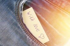 Den pappers- anmärkningen med inskriften älskar jag dig, med förälskelsepip ut ur facket av jeansbyxa Begreppet av dagen av vänne Fotografering för Bildbyråer