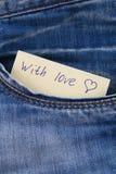 Den pappers- anmärkningen med inskriften älskar jag dig, med förälskelsepip ut ur facket av jeansbyxa Begreppet av dagen av vänne Arkivbild