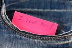 Den pappers- anmärkningen med inskriften älskar jag dig, med förälskelsepip ut ur facket av jeansbyxa Begreppet av dagen av vänne arkivfoto