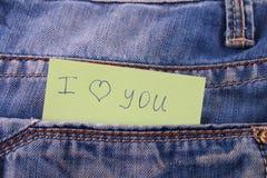 Den pappers- anmärkningen med inskriften älskar jag dig, med förälskelsepip ut ur facket av jeansbyxa Begreppet av dagen av vänne royaltyfri fotografi