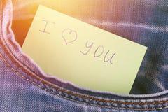 Den pappers- anmärkningen med inskriften älskar jag dig, med förälskelsepip ut ur facket av jeansbyxa Begreppet av dagen av vänne royaltyfri foto