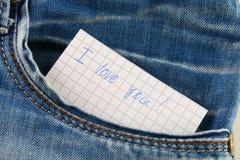 Den pappers- anmärkningen med inskriften älskar jag dig, med förälskelsepip ut ur facket av jeansbyxa Begreppet av dagen av vänne royaltyfria bilder