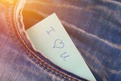 Den pappers- anmärkningen med inskriften älskar jag dig, med förälskelsepip ut ur facket av jeansbyxa Begreppet av dagen av vänne royaltyfria foton