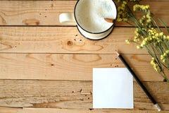 Den pappers- anmärkningen och koppen av nytt mjölkar Arkivfoto