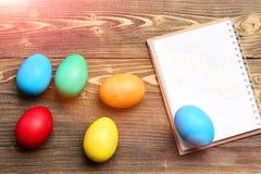 Den pappers- anteckningsboken och färgrika easter ägg, matlagning och menyn planlägger Arkivbild