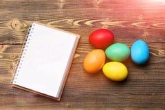 Den pappers- anteckningsboken och färgrika easter ägg, matlagning och menyn planlägger Royaltyfri Fotografi