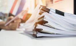 Den pappers- bunten, högen av oavslutade dokument på kontorsskrivbordet gällde royaltyfria bilder