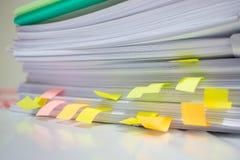 Den pappers- bunten, högen av oavslutade dokument på kontorsskrivbordet gällde royaltyfri foto