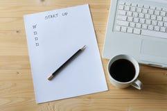 Den pappers- kontrolllistan för startar upp affärsbärbara datorn och kaffe Royaltyfria Foton