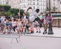 Den Paris skateboradåkaren hoppar den plast- barrikaden, som folket ser på Fotografering för Bildbyråer