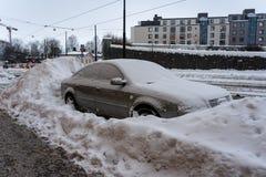 Den parkerade bilen i staden har omgivits av stora belopp av snö royaltyfri bild