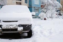 Den parkerade bilen som täckas med snö - snöa stormen, bil efter ett tungt snöfall, mycket snö på bilen, bil i den snöig gården fotografering för bildbyråer
