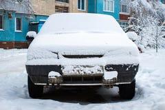 Den parkerade bilen som täckas med snö - snöa stormen, bil efter ett tungt snöfall, mycket snö på bilen, bil i den snöig gården royaltyfri bild