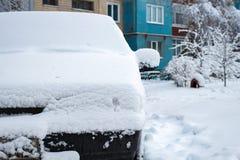 Den parkerade bilen som täckas med snö - snöa stormen, bil efter ett tungt snöfall, mycket snö på bilen, bil i den snöig gården royaltyfria foton