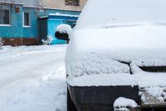Den parkerade bilen som täckas med snö - snöa stormen, bil efter ett tungt snöfall, mycket snö på bilen, bil i den snöig gården royaltyfri fotografi