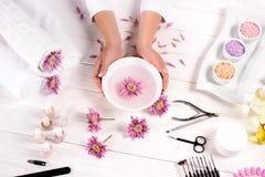 den partiska bilden av kvinnainnehavbadet för spikar över tabellen med blommor, handdukar, det salta färgrika havet, olje- flasko royaltyfri fotografi
