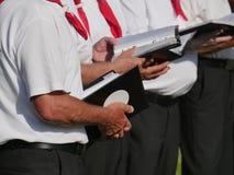 Den partiska sikten av 3 sångare av en kör som rymmer i deras handläroböcker, mörk byxa, vit kort-mufde skjortan, röd sjalett fotografering för bildbyråer