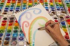 Den pastellfärgade vattenfärgen virvlar runt vid en kompetent konstnär Hand arkivbilder