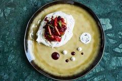 Den Pavlova marängkakan med nya bär och vaniljsås lagar mat med grädde royaltyfri fotografi
