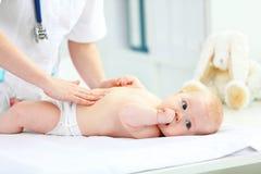 Den pediatriska doktorn undersöker behandla som ett barn magen arkivfoto