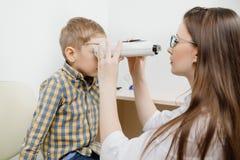 Den pediatriska doktorsögonläkaren kontrollerar vision av barnpojken Begreppsval av exponeringsglaslinser fotografering för bildbyråer